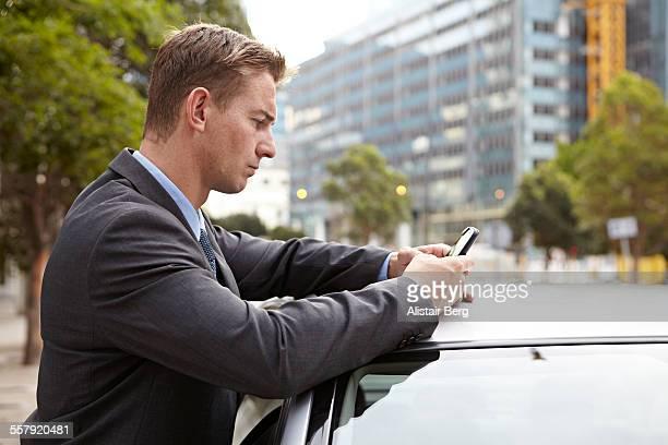 Businessman using smart phone outdoors