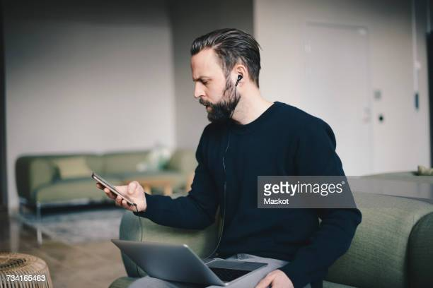 Businessman using smart phone while sitting with laptop on sofa in office lobby