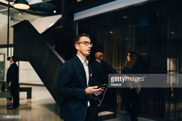 businessman using smart phone while talking through headphones in office - incidental people stock pictures, royalty-free photos & images