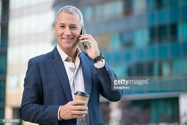 businessman using smartphone  and holding coffee to go outside