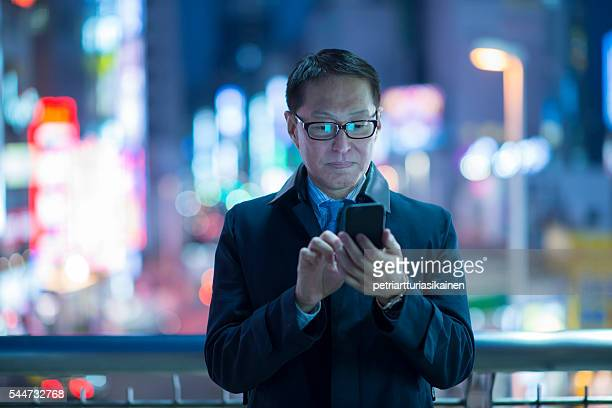 businessman using smartphone at night. - multi colored suit stock photos and pictures
