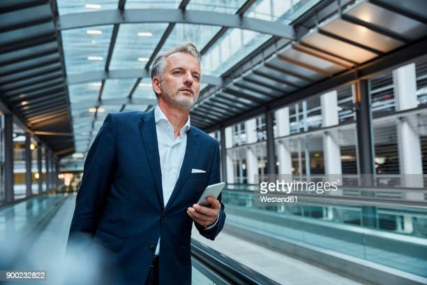 businessman using smartphone at the airport, standing on moving walkway - pedestrian walkway stock pictures, royalty-free photos & images