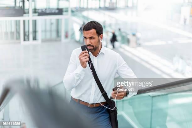 Businessman using smartphone, earphones, on escalator