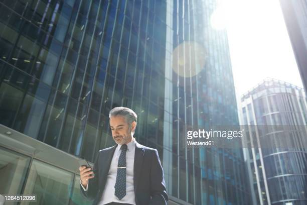 businessman using smartphone in city - architecture stock pictures, royalty-free photos & images