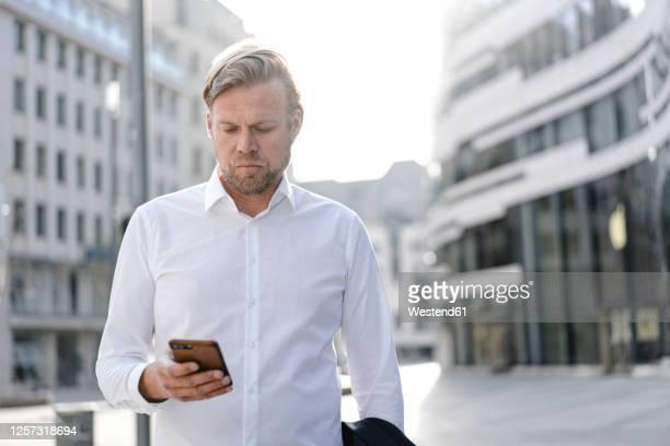 businessman using smartphone in the city - 白いシャツ ストックフォトと画像