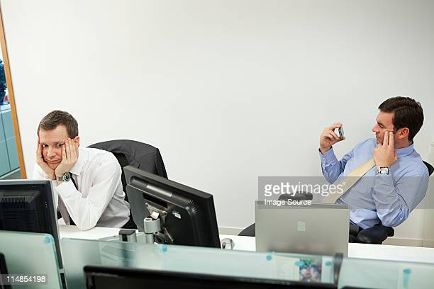 businessman using smartphone, male colleague looking sideways - irritation stock pictures, royalty-free photos & images