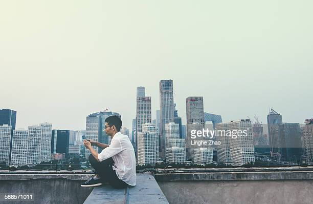 Businessman using smartphone on rooftop