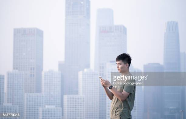 businessman using smartphone on rooftop - building icon stock photos and pictures