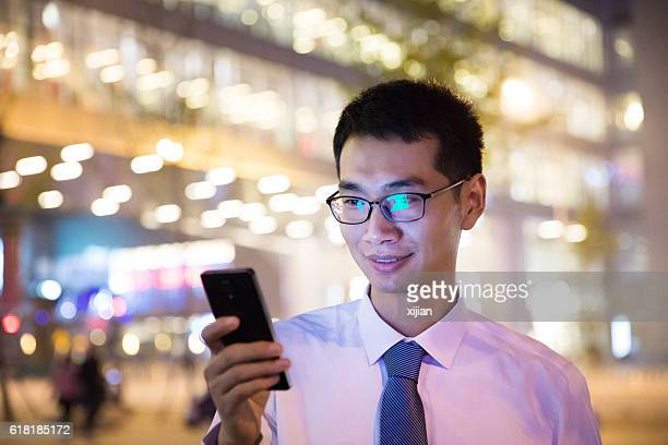 businessman using smartphone outdoors at night