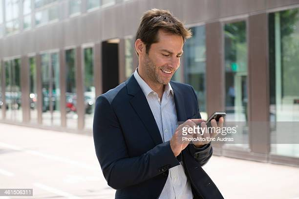 Businessman using smartphone outdoors
