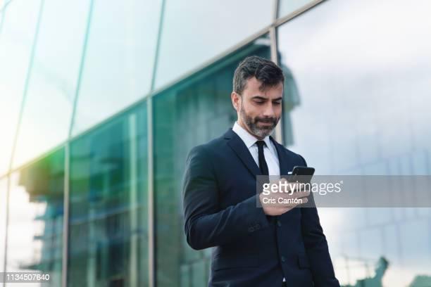 businessman using smartphone - cris cantón photography fotografías e imágenes de stock