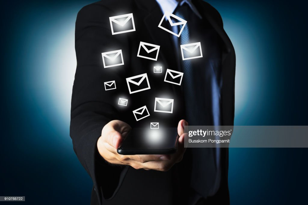 Businessman using smartphone sending massage with email icon : Stock Photo