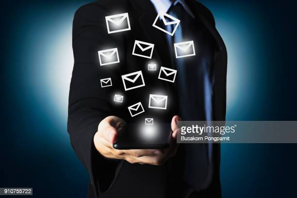 businessman using smartphone sending massage with email icon - marketing icons stock photos and pictures