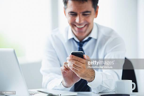 Businessman using smartphone, smiling
