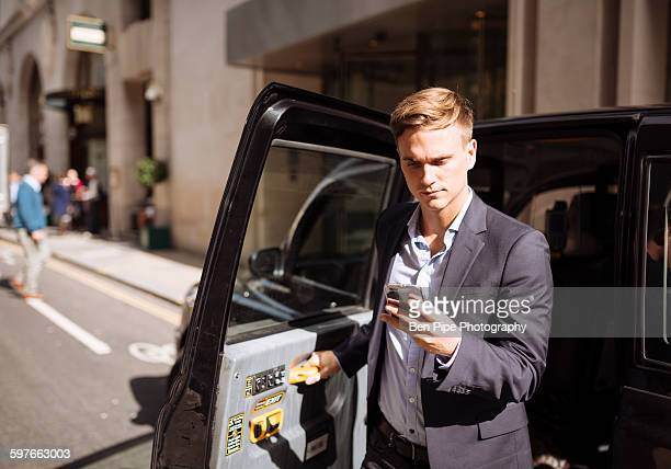 Businessman using smartphone while exiting black cab, London, UK