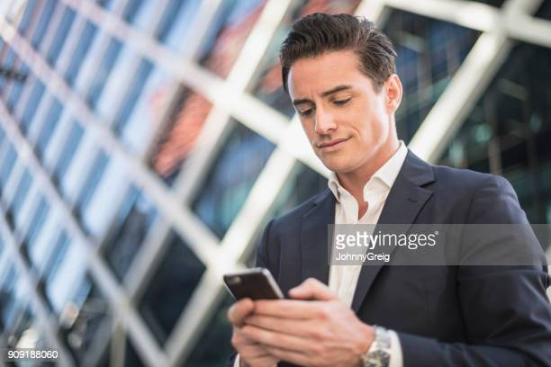 businessman using smartphone with modern building in background - open collar stock photos and pictures