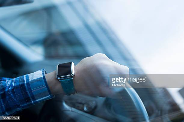 Businessman using smartwatch in the car