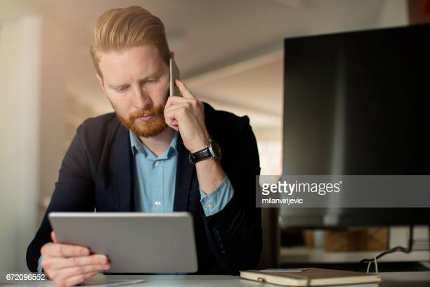 Businessman using tablet and takling on mobile phone