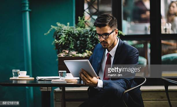 Businessman using tablet at cafe