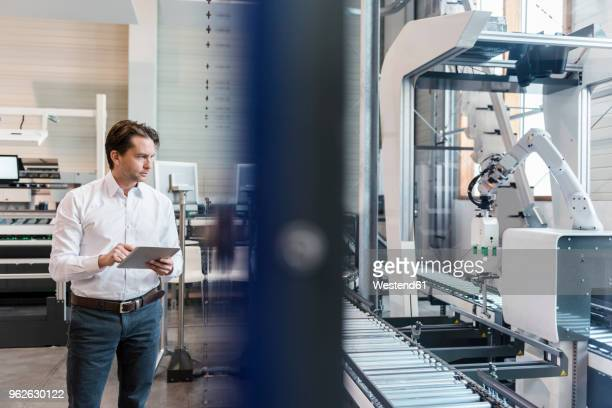 businessman using tablet at conveyor belt in factory - fließbandfertigung stock-fotos und bilder