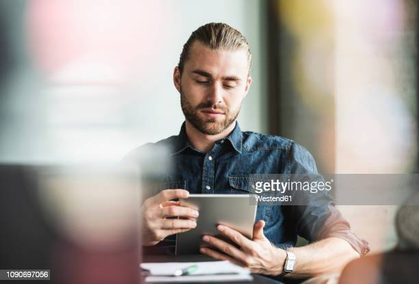 businessman using tablet at desk in office - using digital tablet stock pictures, royalty-free photos & images