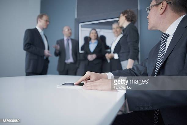 Businessman using tablet computer in office meeting