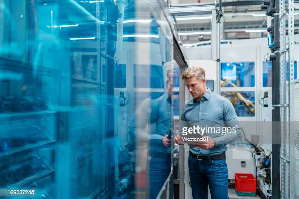 businessman using tablet in a modern factory - fabricage apparatuur stockfoto's en -beelden
