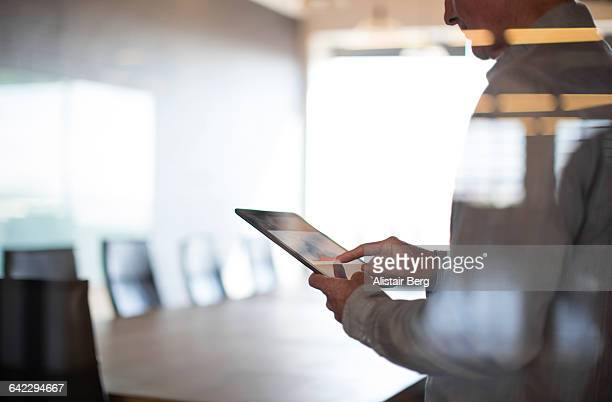 businessman using tablet in conference room - apparatuur stockfoto's en -beelden