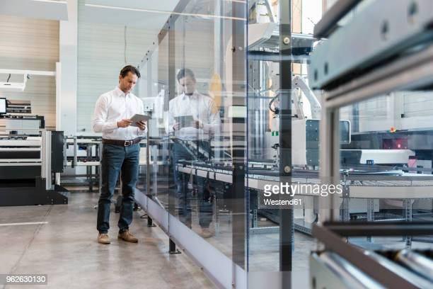 businessman using tablet in modern factory - one man only stock pictures, royalty-free photos & images