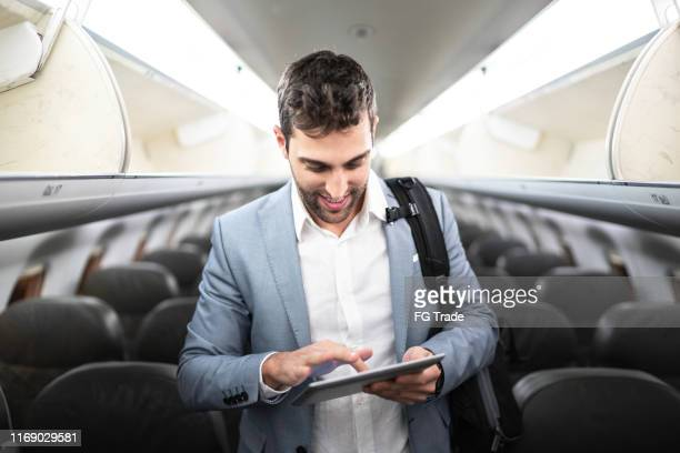 businessman using tablet on airplane - one man only stock pictures, royalty-free photos & images