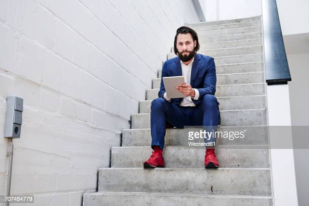 Businessman using tablet on stairs