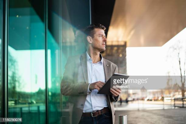businessman using tablet outside a building in the city - anticipation stock-fotos und bilder