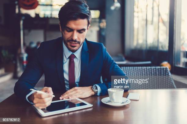 Businessman using tablet pc in cafe
