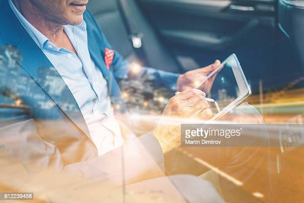Businessman using tablet pc in car