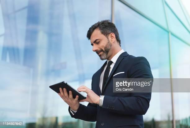businessman using tablet - cris cantón photography fotografías e imágenes de stock