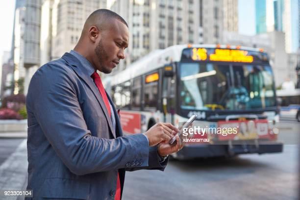 シカゴのダウンタウンでタクシーのアプリを使用しての実業家 - クラウドソーシング ストックフォトと画像