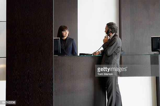 Businessman using telephone at reception desk