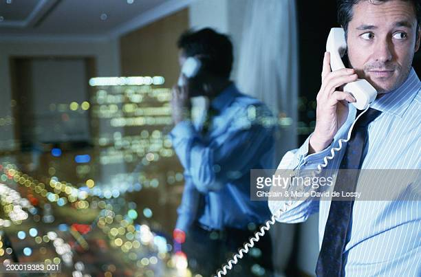 Businessman using telephone, reflection and view seen in window, night