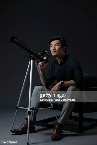 businessman using telescope - 中国北東部 ストックフォトと画像