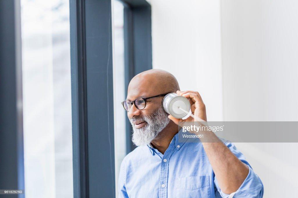 Businessman using tin can phone : Stock Photo