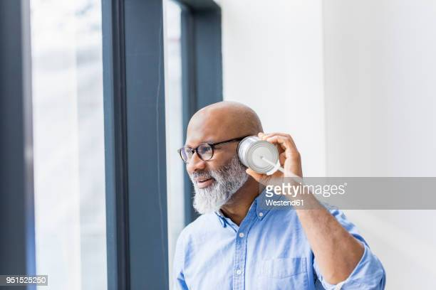 Businessman using tin can phone