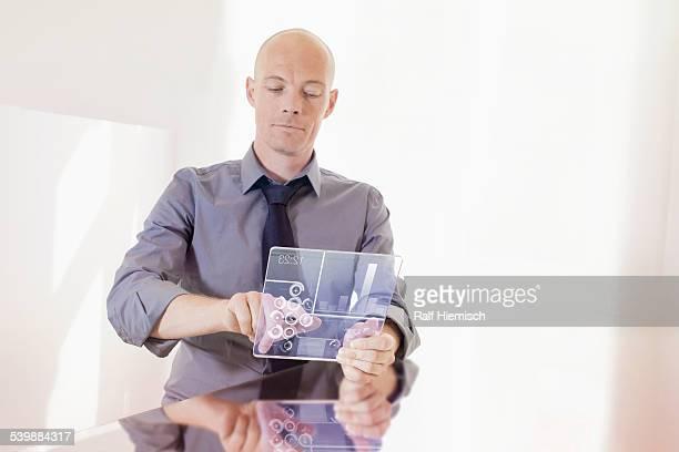 Businessman using transparent digital tablet at desk in office