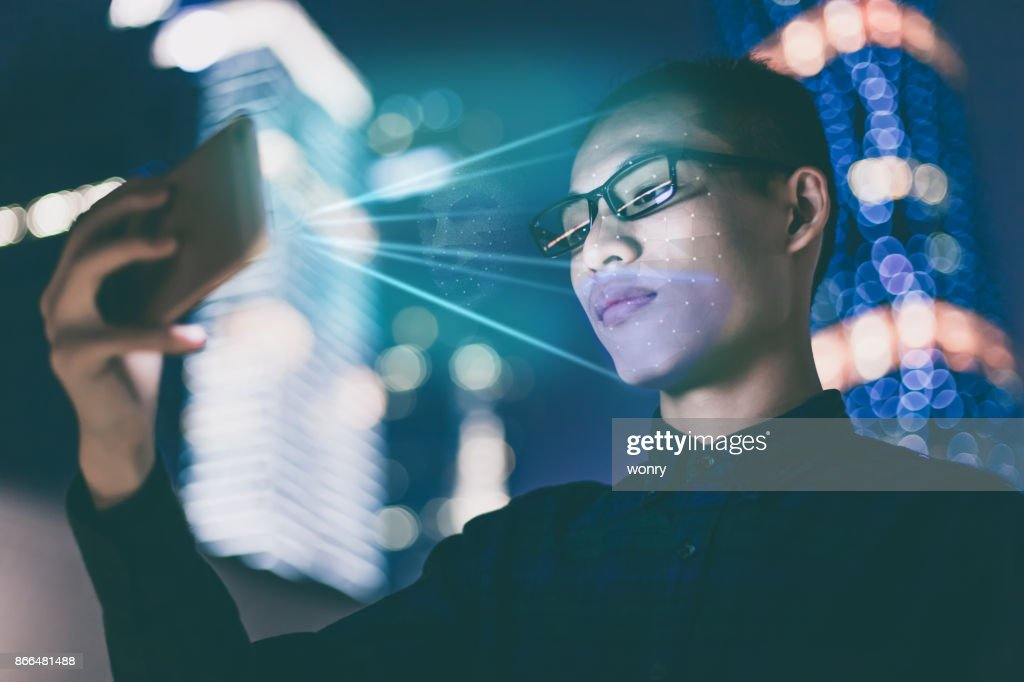 Businessman using using face recognition outdoors : Stock Photo