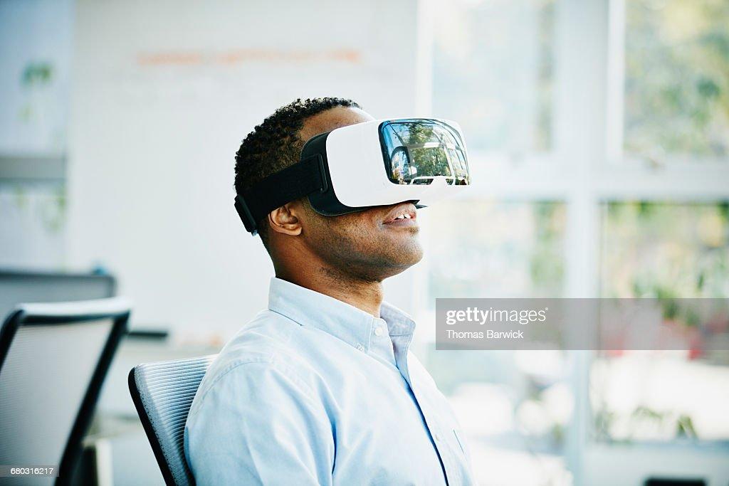 Businessman using virtual reality headset : Stock Photo