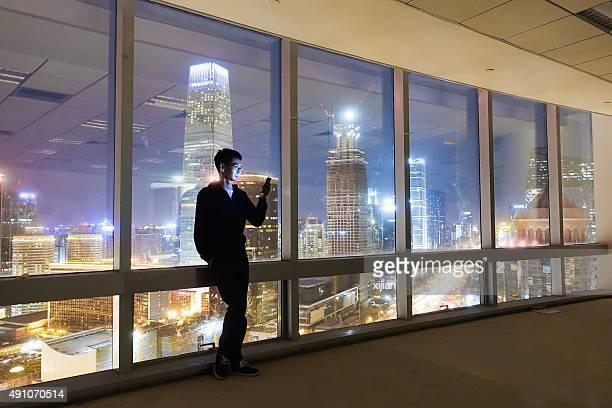 Businessman usinging smart phone at city night