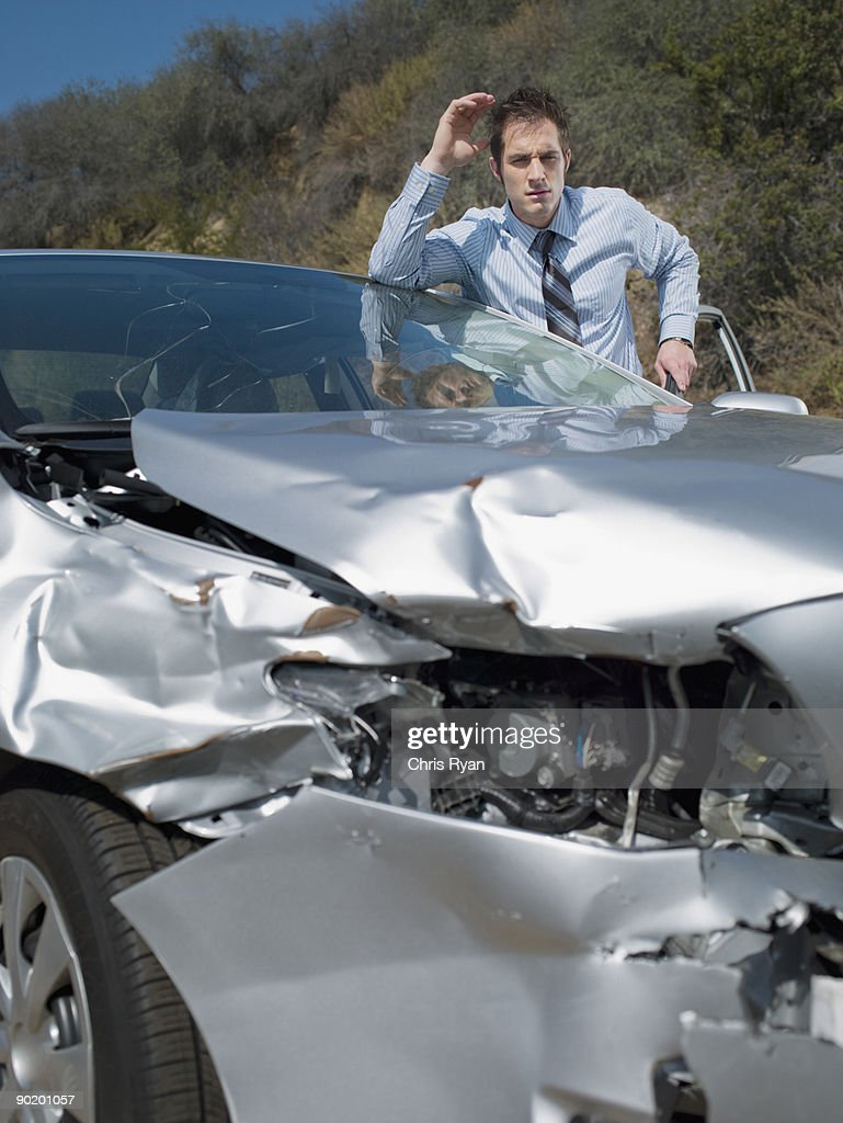 Businessman viewing damaged car front-end : Stock Photo