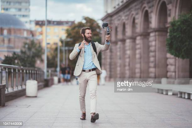 businessman vlogging on business trip - mid adult men stock pictures, royalty-free photos & images