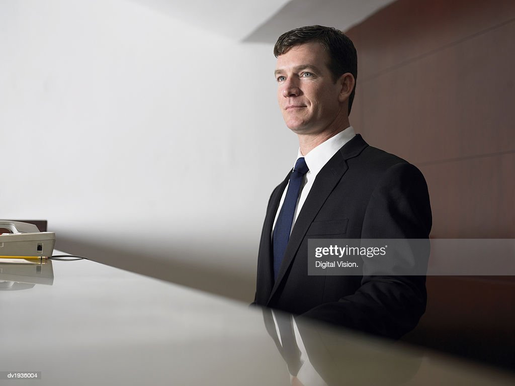 Businessman Waiting at a Reception Desk : Stock Photo