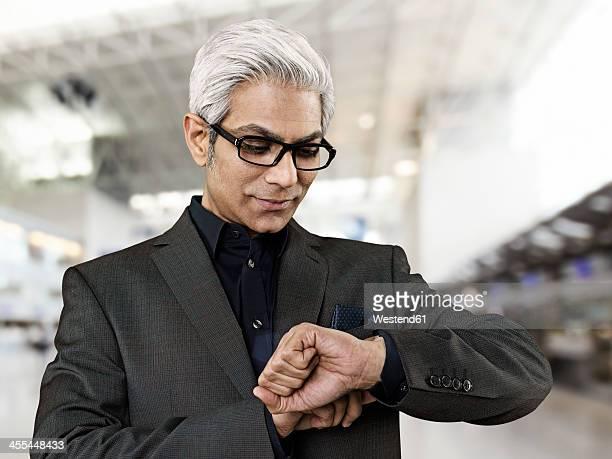 Businessman waiting at airport, smiling