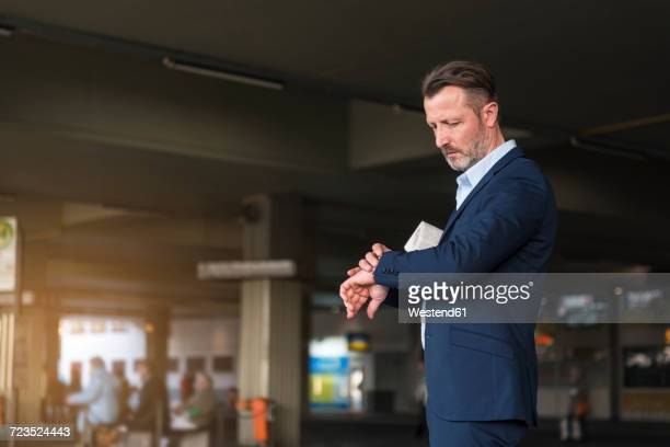 businessman waiting at bus terminal checking the time - time management stock photos and pictures